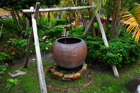 Large clay cauldron hung on wooden stick structure, over a brick fire pit, in a garden surrounded by green bushes, yellow-leaved palm trees. Foto de archivo