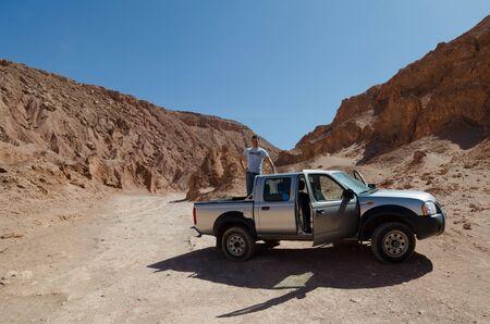 vastness: Man standing on 4WD back in Valle de la Muerte, Chile