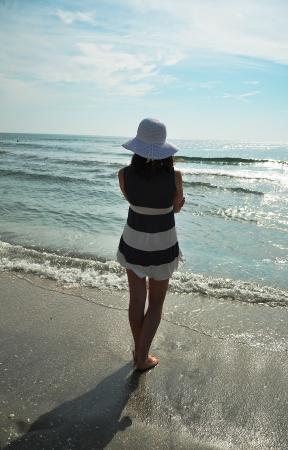 gentle dream vacation: Woman with hat watching the sea Stock Photo