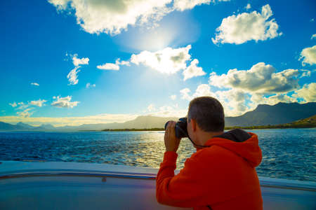 traveler in the orange jacket on the boat in the Indian Ocean near the coast of Mauritius photo