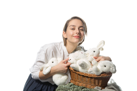 Young girl smiling and hugging a lot of white fluffy rabbit in a wicker basket with a branch of blue sprucegirl and white rabbits photo