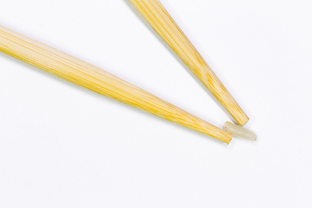 two wooden chopsticks for sushi took one grain of rice photo