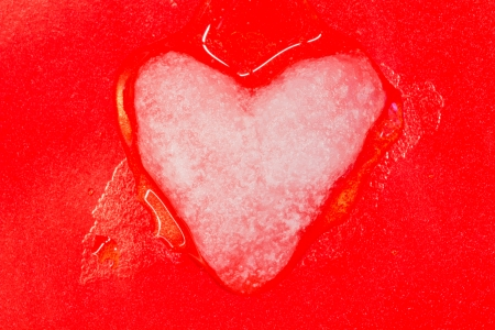 broken relationship: ice cold heart made of snow melts with love on a red background