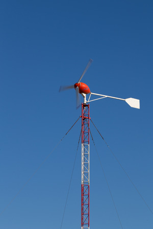 generates: red windmill generates electricity against the clear blue sky