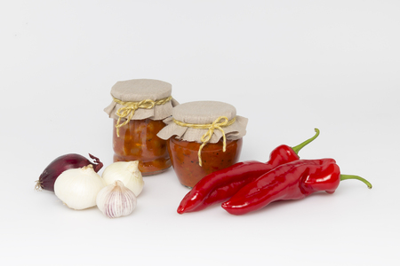 Two glass jars with tinned vegetables and red pepper, onion, garlic on a white background  photo