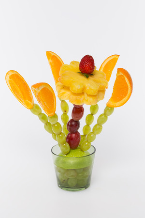 bouquet of fruit with pineapple, grapes, apples and strawberries on a white background photo