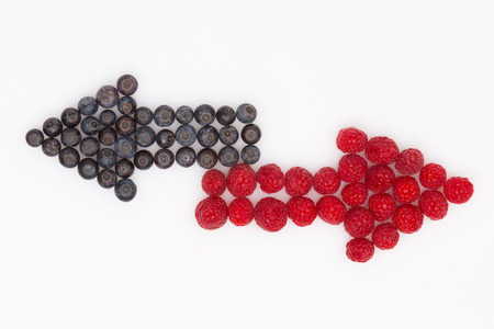 multidirectional: multidirectional arrows of fresh blueberries and raspberries