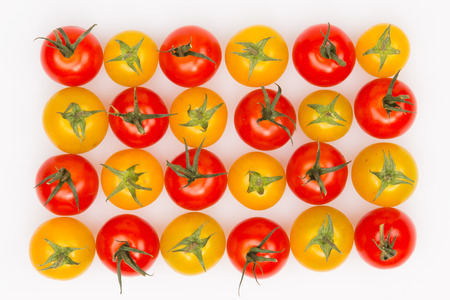 yellow and red tomatoes with green sepals on a white photo