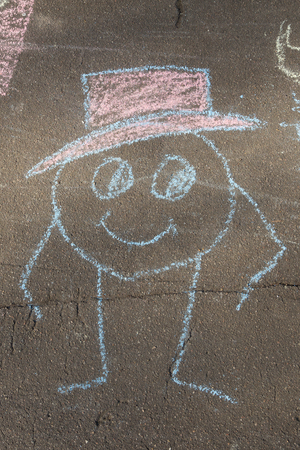 man in a hat drawn with chalk on asphalt