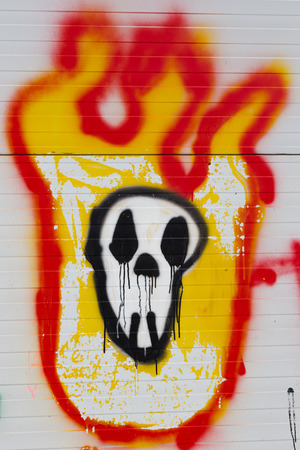 deface: Fire skull graffiti on a street fence