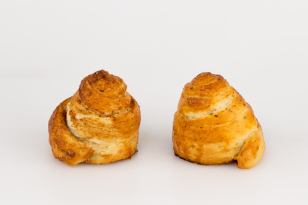 two sweet buns with cinnamon sugar similar to spiral on white background