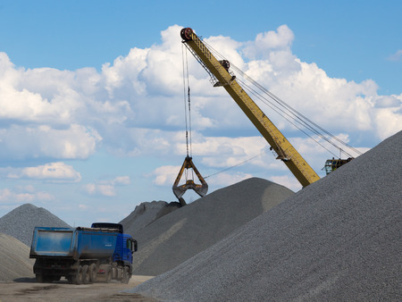 bucket loading in a truck and a big pile of gravel gray against the blue sky with cumulus clouds  photo