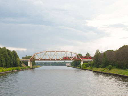 Arched railway bridge over the river in the summer when it is cloudy and Edith red train photo
