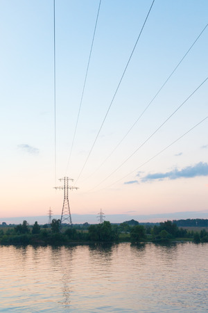 electric wires pass through the river at sunset in summer photo