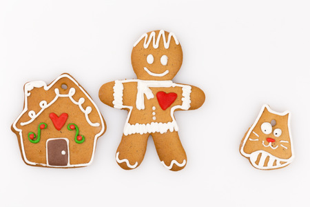house, a cat and a man with a red heart were made of gingerbread on white background photo