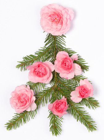 tree marigold: Christmas tree made of green branches with needles decorated with pink roses on a white background  Stock Photo