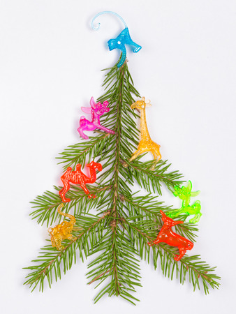 Christmas tree made of fir branches decorated with bright colored toy animals on a white background  photo