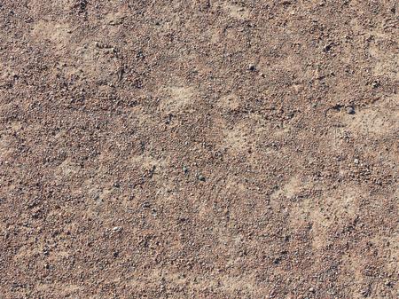 未舗装の道路上の茶色の砂利の微細組織