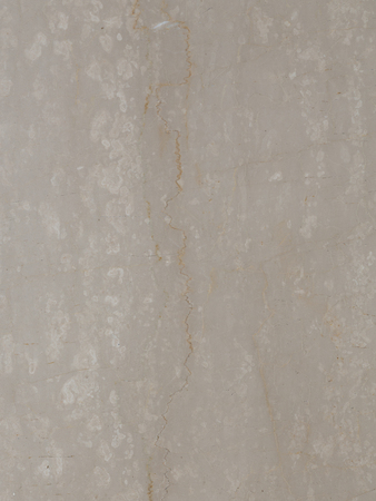 large slab of solid smooth beige marble with brown streaks and light spots