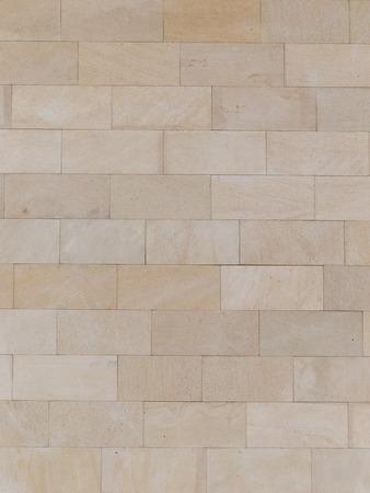 vertical brick wall made of light beige natural travertine