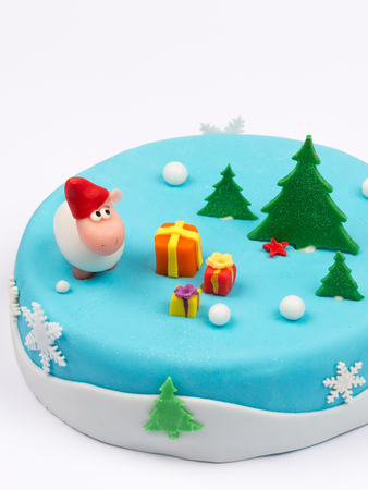 beautiful delicious sponge cake with symbols, the sheep and decorated Christmas trees with gifts snow snowflake photo