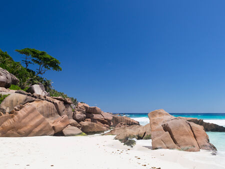 peaceful scene: wonderful scenic sea beach with big rocks and trees and clear skies in the Seychelles Stock Photo