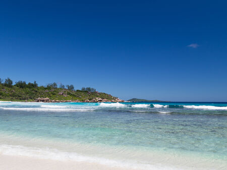 big island: horizontal seascape with pristine scenic sea beach with big stones and hard-to- reach shore beautiful waves Coconut Beach on the island of La Digue, Seychelles