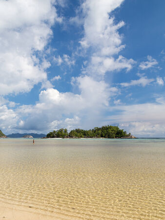 man walking on the water on a beautiful tropical small island with palm trees and clean salt water Indian Ocean in Seychelles photo