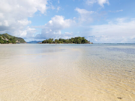 beach scene: small beautiful tropical island with palm trees and clean salt water Indian Ocean, Seychelles