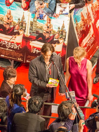 heard: Tokyo - January 27, 2015: Johnny Depp gives interviews and Amber Heard in a fuchsia dress at the launch of the film Mortdecai, against the background of the posters in Japanese January 27, 2015, Tokyo, Japan Editorial