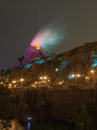 theme parks: Tokyo - January 26, 2015: The current artificial volcano and beautiful evening light in the Disney Theme Parks See January 26, 2015, Tokyo, Japan Editorial