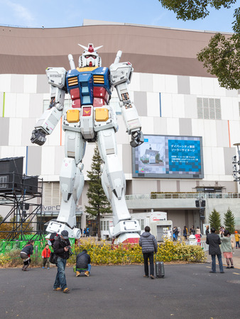 Tokyo - February 7, 2015: A giant space robots at the entrance to the store and people are photographed with him Feb. 7, 2015, Odaiba, Tokyo, Japan