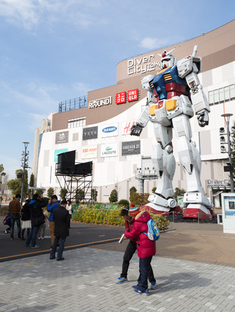 animated alien: Tokyo - February 7, 2015: A huge robot at the entrance to the store and people are photographed with him Feb. 7, 2015, Odaiba, Tokyo, Japan
