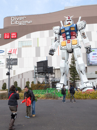 animated alien: Tokyo - February 7, 2015: A giant robot trnsformer at the entrance to the store and people walk around and photographed February 7, 2015, Odaiba, Tokyo, Japan