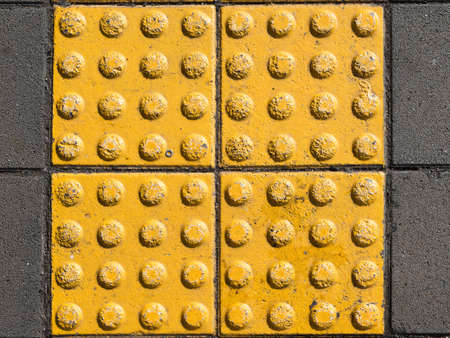 visually: yellow concrete tiles with texture on the sidewalk is for the blind