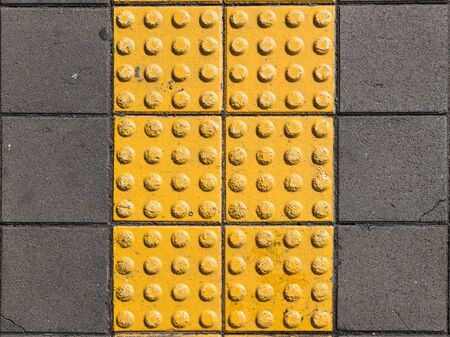 visually: yellow concrete tile with texture in the form of a strip on the sidewalk is for the blind