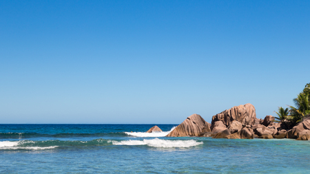large formation: large granite pink stones in the Indian Ocean with beautiful waves in Seychelles