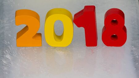brightly colored numbers 2018 calendar reflected in the surface of the ice photo