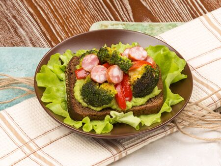 veal sausage: bright beautiful healthy nutritious delicious sandwich made of veal sausage fried broccoli and red pepper Stock Photo