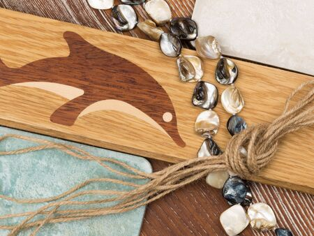 mother of pearl: marine theme in interior design with artistic parquet with inlaid dolphin, aged ceramic tiles, mother of pearl beads, wood and twine salted Stock Photo