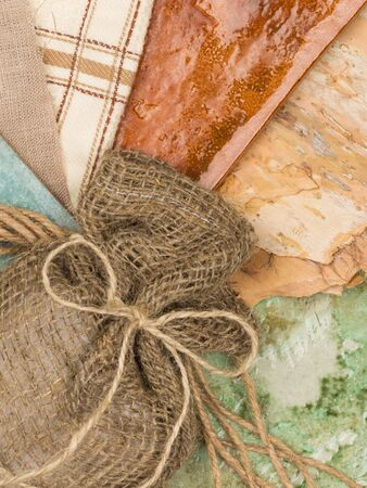 linen bag: a linen bag with a bow of twine, bark, wood, ceramic tiles in warm colors in a country style and denim Stock Photo