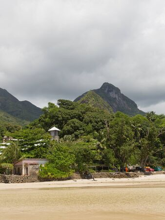 locals: Mahe - November 12, 2014: View on the coast of the island of Mahe with the water, where you can see the mountains, a Catholic church, built and locals going about their business November 12, 2014, Mahé, Seychelles