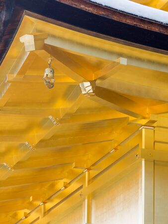 rafters: Kyoto - January 31, 2015: The lower part of the roof of the ancient Golden pavelona in Kyoto, covered with real gold is one of the main attractions of Kyoto January 31, 2015 in Kyoto, Japan