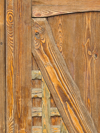 precipitation: old wooden decorative element of golden oak with flaky paint in the style of the country, damaged by weather precipitation in the street