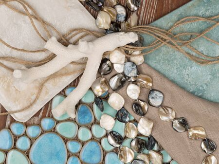 seed beads: selection of materials in a nautical theme with a blue ceramic mosaic-like sea pebbles, a linen cloth, pearl beads, salted wood, twine and coral