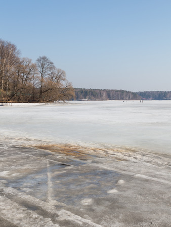 stubbornness: Lake in the early spring and the ice starts melting off the coast, and in the distance the fishermen go on dangerous ice