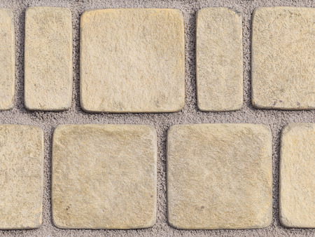 rounded edges: light textured paving tiles imitating stone path with rounded edges and seams are covered with fine marble chips Stock Photo