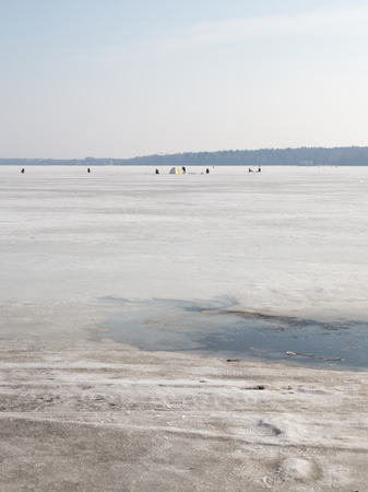 stubbornness: ice melts, but despite the danger of falling through the ice, fishermen continue to fish on the lake in early spring Stock Photo