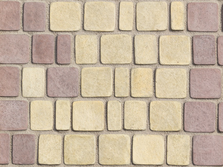 rounded edges: textured paving tiles imitating stone path with rounded edges and seams are covered with fine beige marble chips