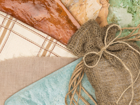 linen bag: a linen bag with a bow of twine, bark  wood, ceramic tile warm bright colors in a country style and rough natural fabric